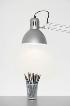 Pencil holder under adjustable lamp over white background