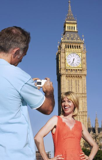 Husband taking photo of wife by Big Ben Tower London England