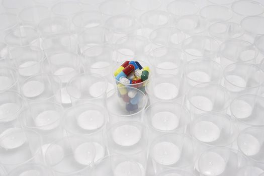 Plastic cup containing pills surrounded by empty glasses