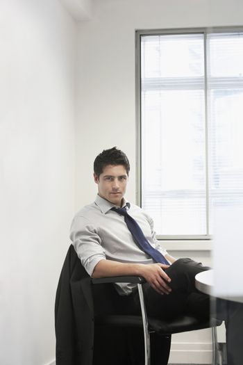 Portrait of a serious businessman sitting at desk in office