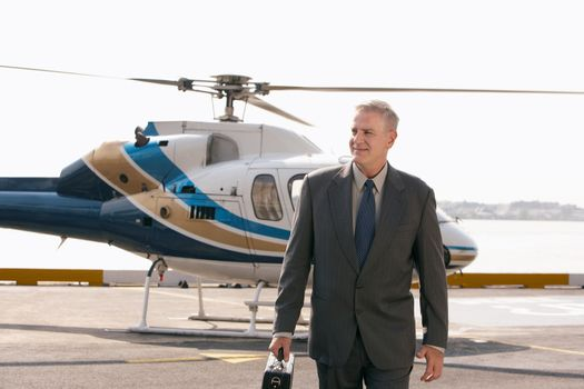 Smart middle aged businessman arriving on helicopter pad