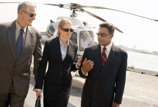 Three multiethnic businesspeople arriving from helicopter