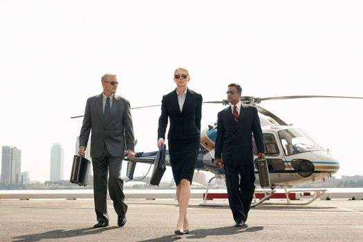 Full length of smart multiethnic businesspeople arriving from helicopter