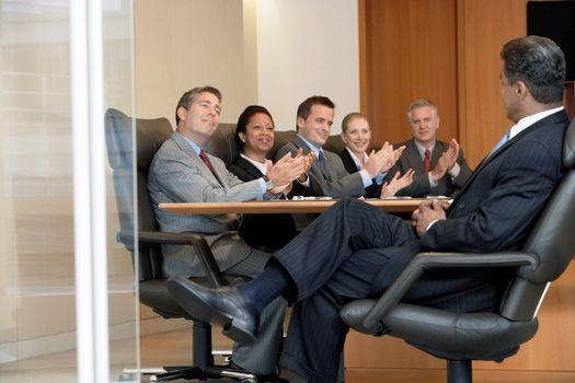 Business people applauding man in office meeting