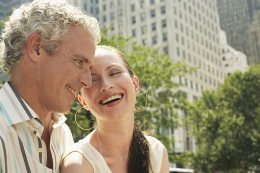 Caucasian couple smiling together with building in the background
