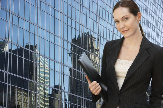 Portrait of a businesswoman with folder in front of commercial building