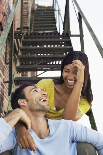 Couple sitting on fire escape stairs