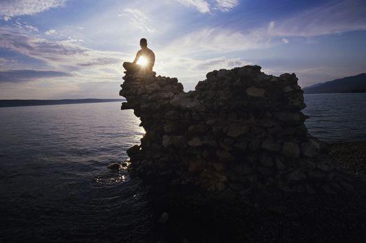 Man sitting on rock overlooking ocean