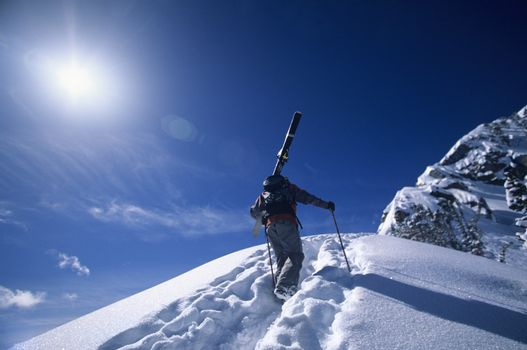 Skier hiking to mountain summit