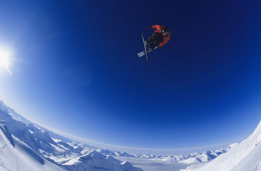 Skier jumping against blue sky
