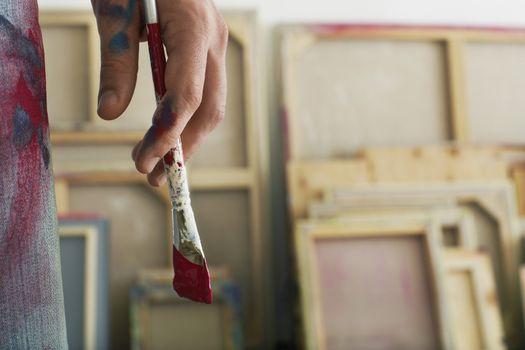 Closeup of an artist holding paintbrush
