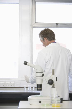 Scientist working behind microscope in laboratory