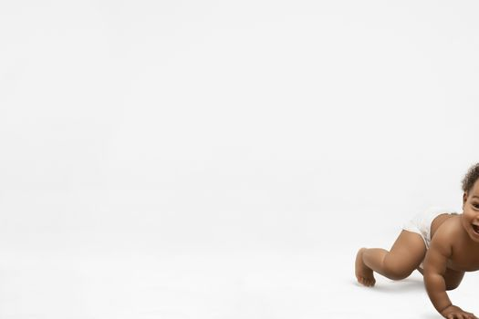 Cute little boy crawling on white background