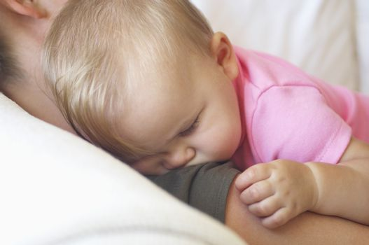 Closeup of a baby sleeping on mother's shoulder