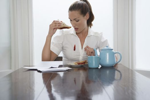 Beautiful woman looking at stain on shirt while having breakfast
