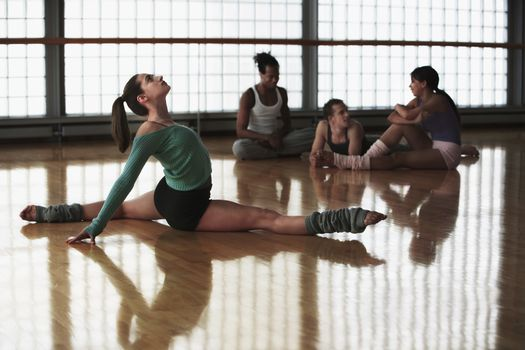 Young female practicing aerobics with friends in the background