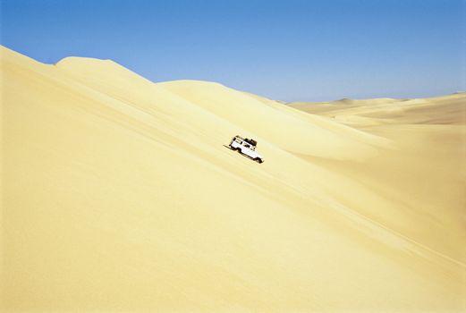 Safari vehicle driving in desert