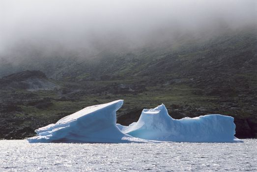 Small iceberg in front of rocks