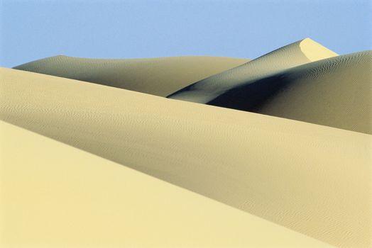 Sand dunes against clear sky