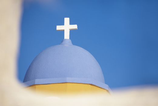 Cross on the dome of church over blue sky