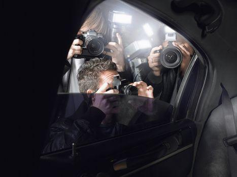 Paparazzi taking pictures through car window