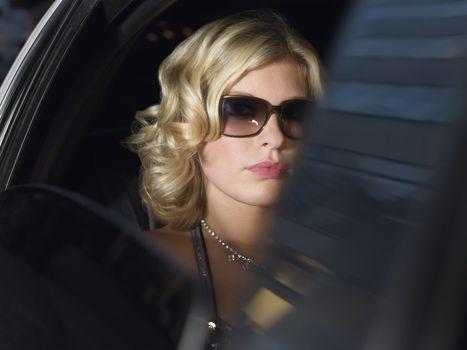 Elegant female celebrity wearing sunglasses in limousine