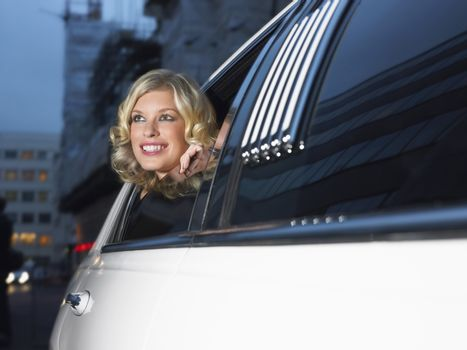 Smiling young female celebrity in limousine looking out of window
