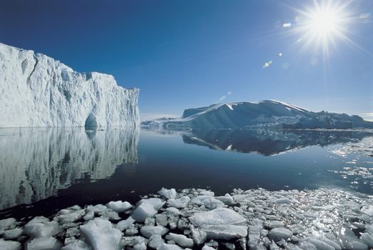 Sun over icebergs and ocean