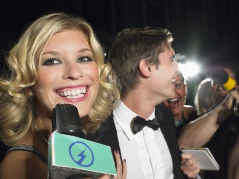 Smiling young female celebrity talking into microphone with paparazzi in background