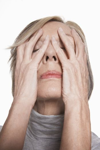 Closeup of a senior woman with hands on her face against white background