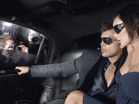 Young celebrity couple in limousine with paparazzi by window
