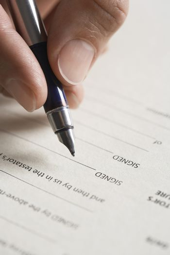 Closeup of a hand signing document