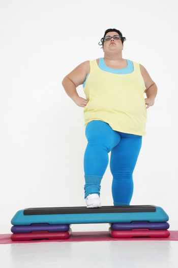 Full length of a plus size woman on exercise steps against white background