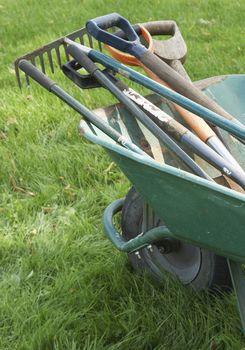 Closeup of gardening tools in cropped wheelbarrow on grass
