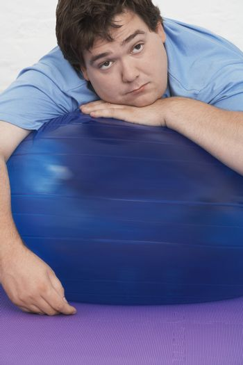 Portrait of an overweight man resting on exercise ball in health club