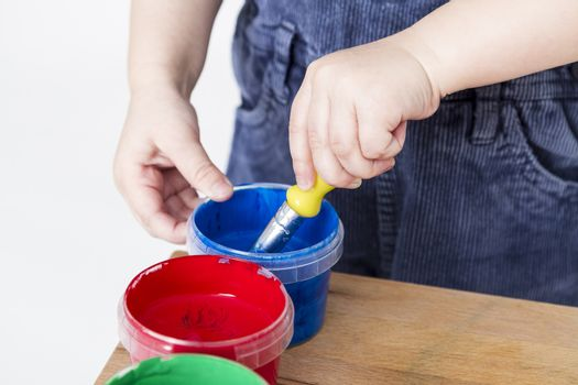 child holding brush in blue paint tub