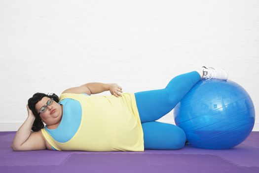 Overweight woman doing leg exercise with exercise ball at healthclub