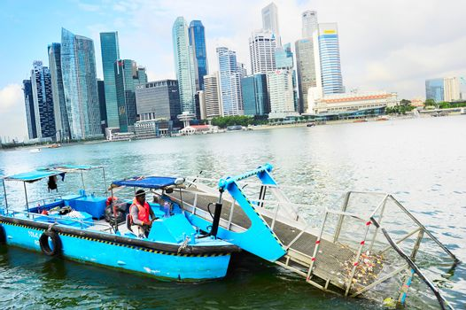 Singapore, Republic of Singapore - March 8, 2013: Water surface cleaning boat removing the garbage from the river in front of Singapore downtown