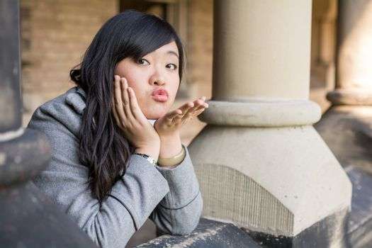young woman leaning forward next to stone pillars blowing a kiss