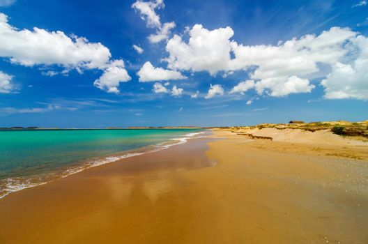 Wide deserted beach with turquoise Caribbean water in La Guajira, Colombia