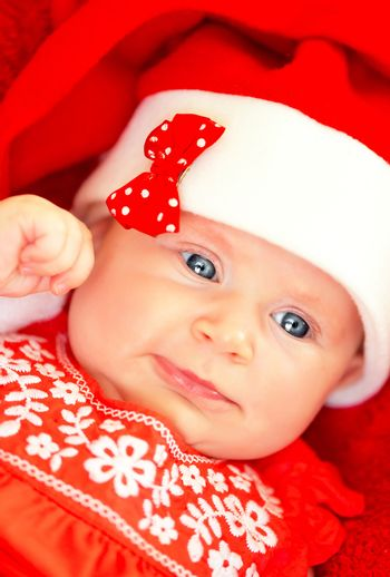 Closeup portrait of sweet little baby girl wearing red festive dress and Santa hat, having fun on Christmas party, wintertime holidays