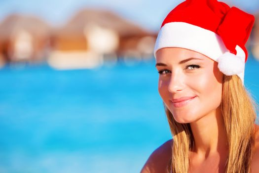 Closeup portrait of cute girl wearing red Santa hat enjoying luxury beach resort, travel to Maldives on Christmas time holidays