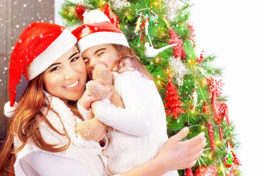 Portrait of attractive woman with daughter celebrate New Year at home, wearing red Santa hats, girl receive as gift soft toy of bear