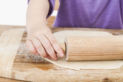 young child rolling out dough for a homemade pie