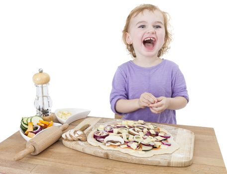 cute laughing child making fresh pizza. studio shot isolated on white background