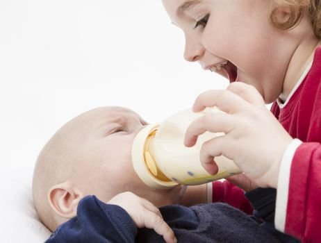 young, happy child feeding toddler with milk bottle in light background