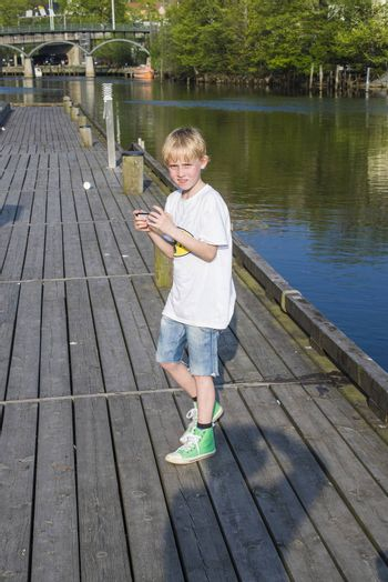 The boy strolling along the Tista River in Halden, Norway with grandpa and check if there is any mail on iPhone