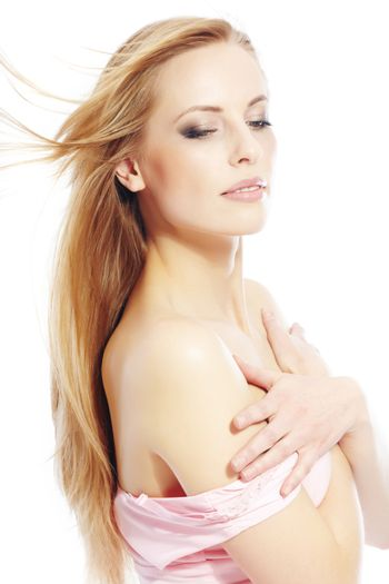 Elegant blond lady on a white background in the pink dress with revealed shoulders
