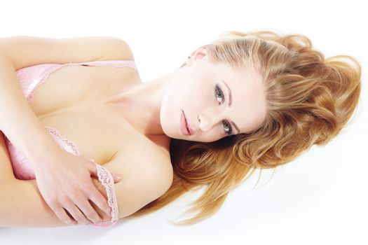 Young lady laying on a white background revealgin her pink brassiere