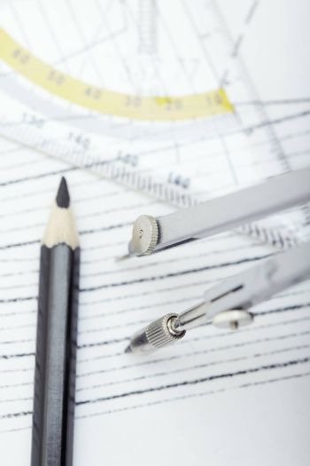 Scheme with drawing tools. Extremely close-up photo. Focus on the compasses
